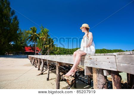 Beautiful woman sitting on a wooden jetty at tropical resort beach