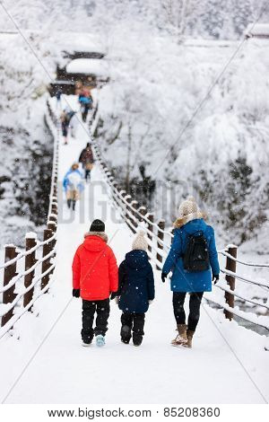 Family of mother and kids crossing the bridge over Shogawa river at historic Japanese village Shirakawa-go at winter, one of Japan's UNESCO world heritage sites