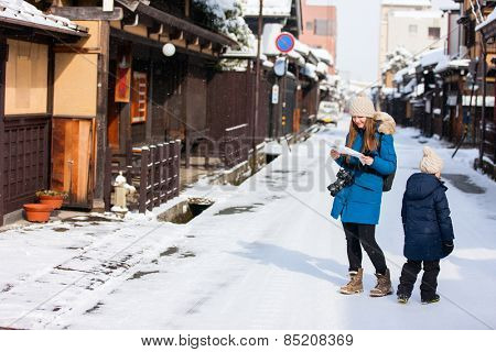 Family of mother and daughter at old district of historical Takayama town in Japan on winter day
