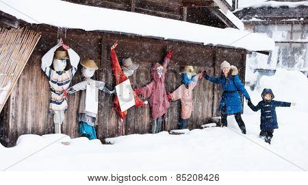 Family of mother and daughter with funny scarecrows at historic Japanese village Shirakawa-go at winter, one of Japan's UNESCO world heritage sites