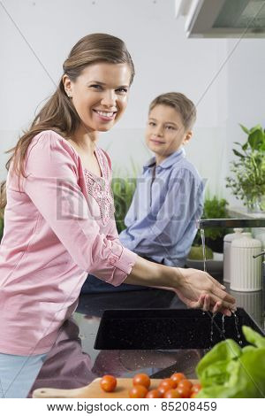 Portrait of smiling woman washing hands with son sitting on counter in kitchen
