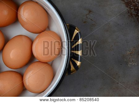 Overhead shot of brown eggs in pot of water. Closeup only half the pot is showing on a well used cooking surface.