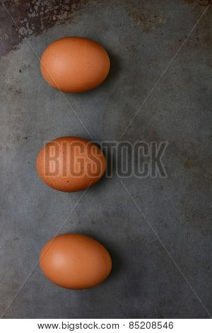 Overhead shot of three organic brown eggs on a metal baking sheet. Vertical format with copy space.
