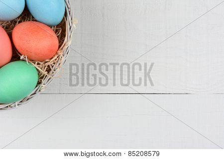 High angle shot of a basket of Easter Eggs in the corner of the frame. The basket is on a rustic white wood kitchen table. Horizontal format with copy space.