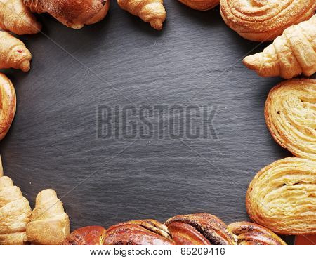 Bakery products arranged as frame on grey board.