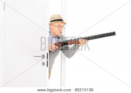 Angry senior with a rifle walking through a door isolated on white background