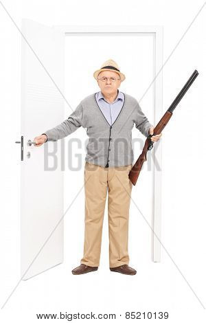 Full length portrait of an angry senior holding a shotgun and walking through a door isolated on white background