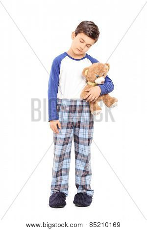 Full length portrait of a sleepy boy holding a teddy bear isolated on white background
