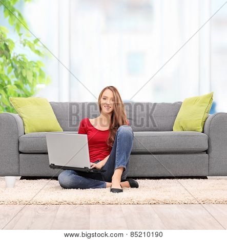 Young woman working on laptop seated on the floor at home shot with tilt and shift lens