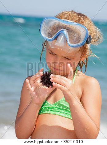 Little girl wearing snorkeling mask looking at sea urchin