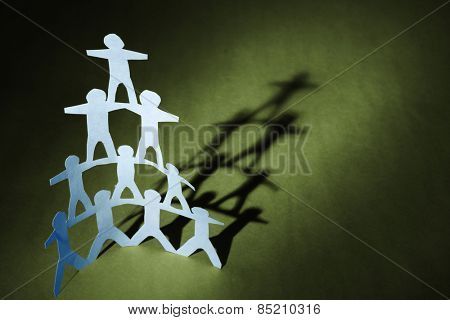 Human team pyramid on green background
