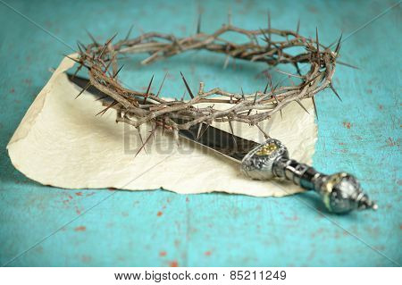 Crown of thorns and Roman sword on vintage paper -Selective focus on crown