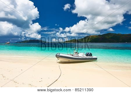 Tropical beach at Seychelles with inflatable boat
