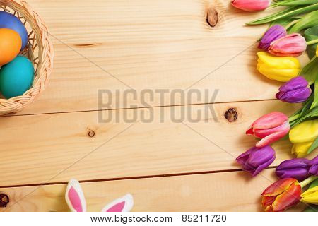 Spring Flowers bunch and easter eggs at wood floor texture. Beautiful Tulips bouquet gift. Easter  background. Springtime or summertime. Invitation card design with space for your text