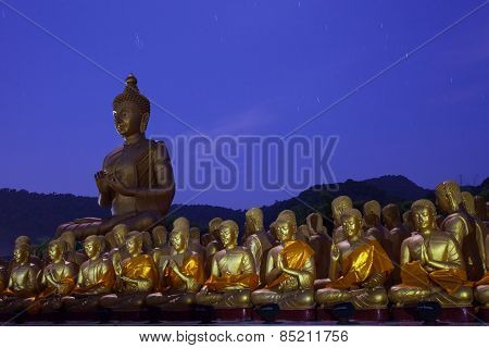 Golden Buddha Statue In Temple With Beautiful With Star Tail Against Blue Night Sky
