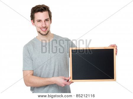 Young casual man holding a blank blackboard