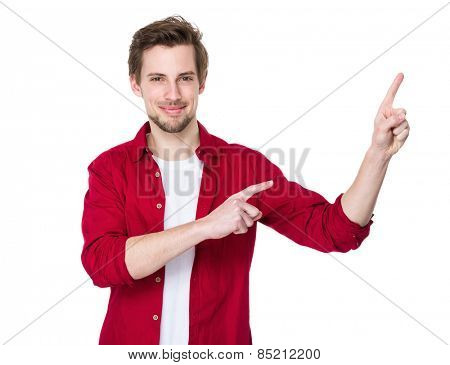 Happy young man pointing to blank space on the right