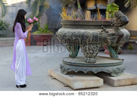 Young Asian woman making a votive offering of fresh pink flowers at an open-air Buddhist shrine filled with burning sticks or incense