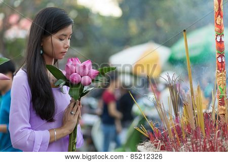 Peace and beauty in prayer as a young Vietnamese woman makes an offering of pretty fresh pink flowers at a Buddhist shrine with burning incense