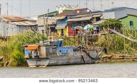 PHNOM PENH, CAMBODIA, JANUARY 2, 2013: Small village and fishing boats mooring at the riverside