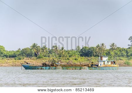 PHNOM PENH, CAMBODIA, JANUARY 2, 2013: A dredger on Mekong river between Phnom Penh and Vietnam border