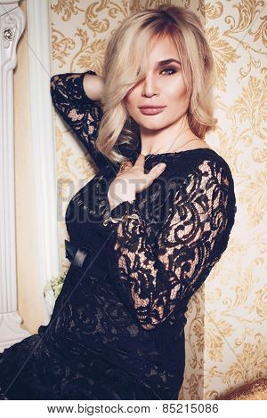 Glamour portrait of beautiful young woman wearing stylish black lace dress posing inside of rich home interior