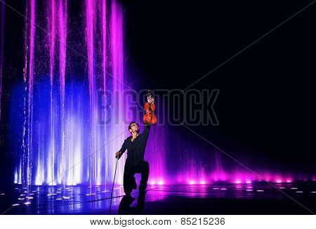 Violin performer with water and light show