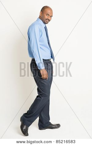 Side view Indian businessman walking and turn back head looking at camera, on plain background.