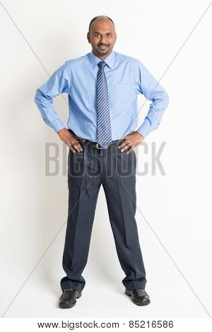 Full body Indian businessman hand on waist looking at camera, standing on plain background with shadow