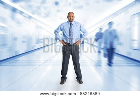 Full body Indian businessman standing at corridor, inside business building with motion blurred people as background.