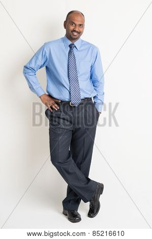 Full body confident Indian businessman standing on plain background with shadow