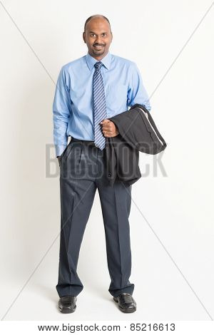 Full length Indian businessman looking at camera, on plain background.