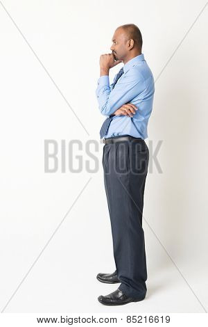 Profile view of full body Indian businessman hand on chin looking at blank copy space, standing on plain background with shadow