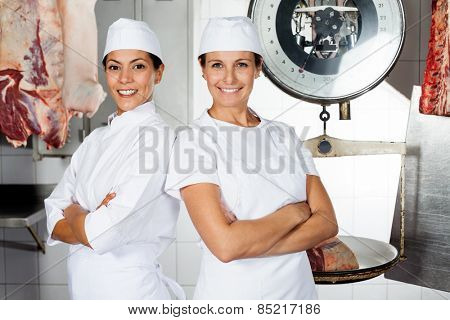 Portrait of happy female butchers standing arms crossed in butchery