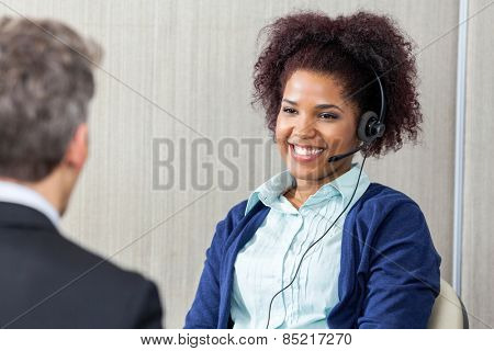 Happy female customer service agent wearing headset looking at manager in office