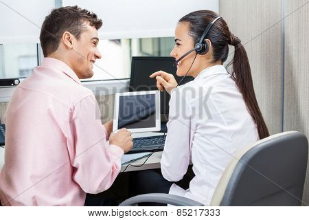 Happy call center representatives discussing while using tablet computer in office