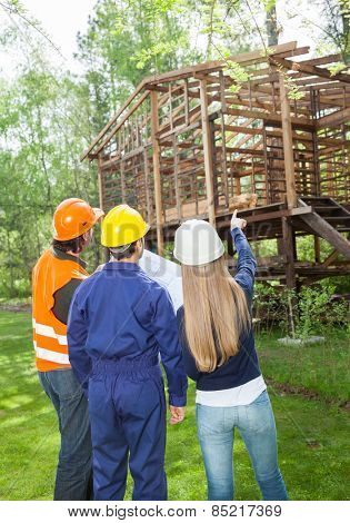 Rear view of male and female architects discussing over incomplete wooden cabin at construction site