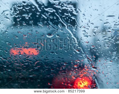 Rainy street traffic lights, view through wet glass. Abstract  background.