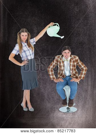 Geeky hipster watering her boyfriend against black background