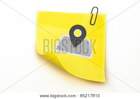 Map marker against sticky note with grey paperclip