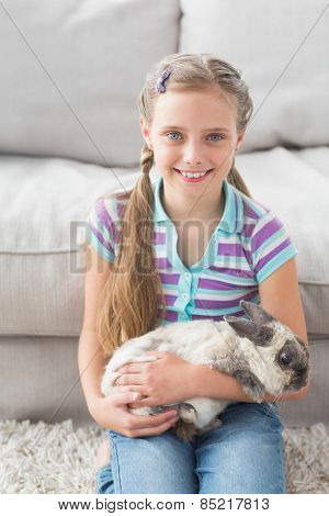 Portrait of cute girl holding rabbit at home in living area