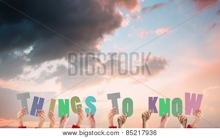 Hands holding up things to know against orange and blue sky with clouds