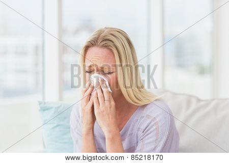 Woman sneezing in tissue in the living room