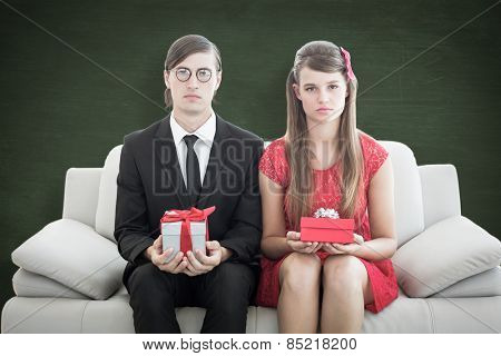 Unsmiling geeky couple with gift against green chalkboard