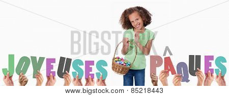 Hands holding up joyeuses pasques against portrait of a cute girl holding a basket full of easter eggs