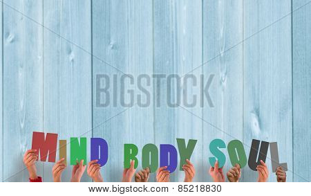Hands holding up mind body soul against wooden planks
