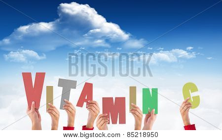 Hands holding up vitamin c against bright blue sky with clouds