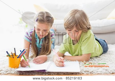 Siblings drawing with colored pencils while lying on rug at home in the living room