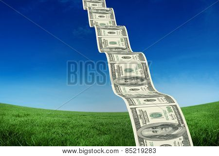 Bumpy dollar road against green field under blue sky