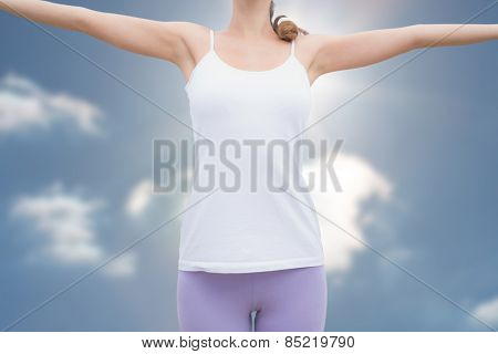 Woman standing with arms raised on countryside landscape against sky